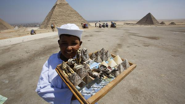 A child vendor waits for tourists to sell them souvenirs at the Giza Pyramids, on the outskirts of Cairo