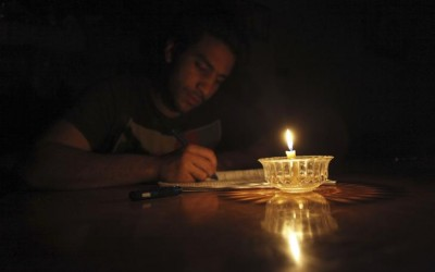 Mostafa Khaled studies by candlelight for his early morning exams during a power cut in Toukh