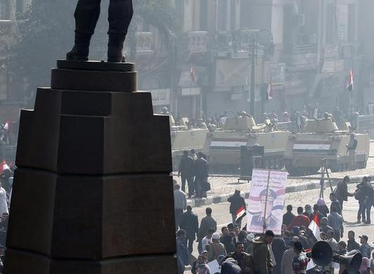 Supporters of Egypt's army and police gesture in front of statue of Egypt's former Army Chief of Staff Abdel Moneim Riad, near Tahrir square in Cairo